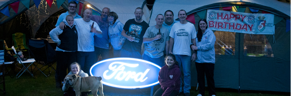 Cheshire Capri Club Members stood behind an illuminated FordDealership sign at Tatton Park Classic Car Show