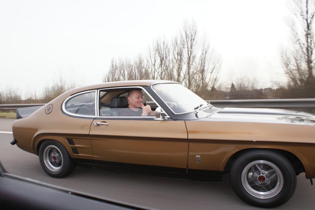 Gold and black custom mk1 ford capri, driving along the m6 motorway at speed on route to the NEC