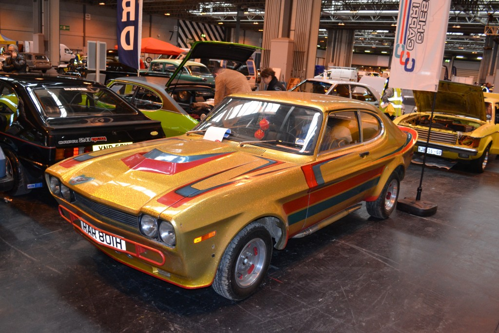 A highly modified Mk1 Capri featuring deep flake gold paint, custom paint graphics, side exit exhausts, lifted rear end on display at NEC