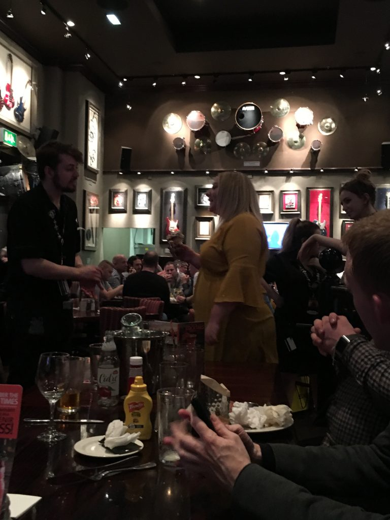 Kasey standing up at HardRock Cafe as the staff and CCC members sing Happy Birthday